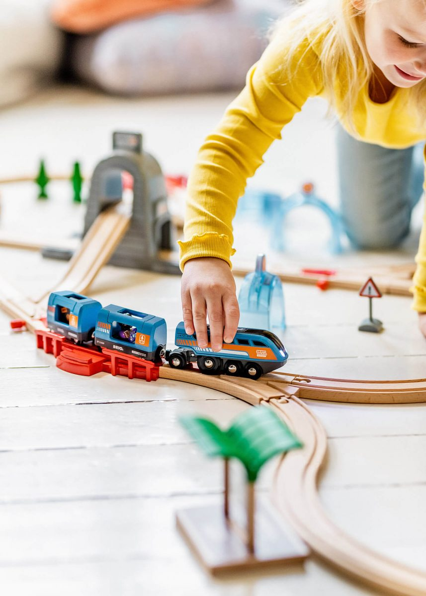 Kid playing with Brio train on floor.