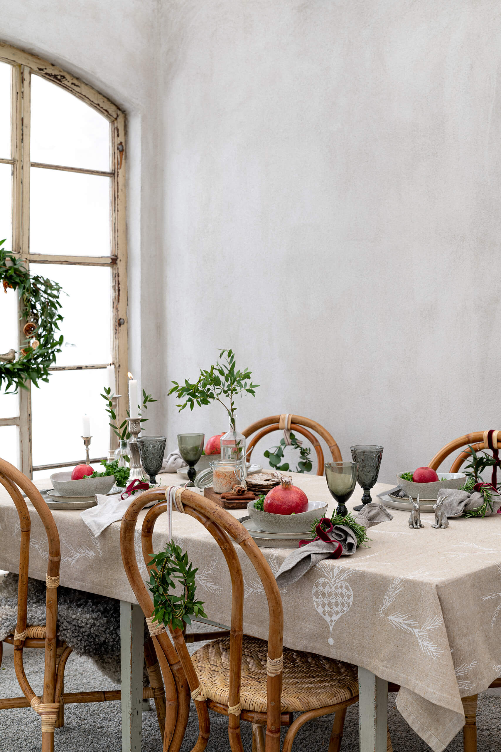 Christmas table by a window, candelabra, plates, glasses och flowers.