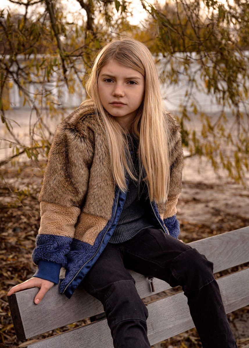 Kid posing on a bench, autumn dressed