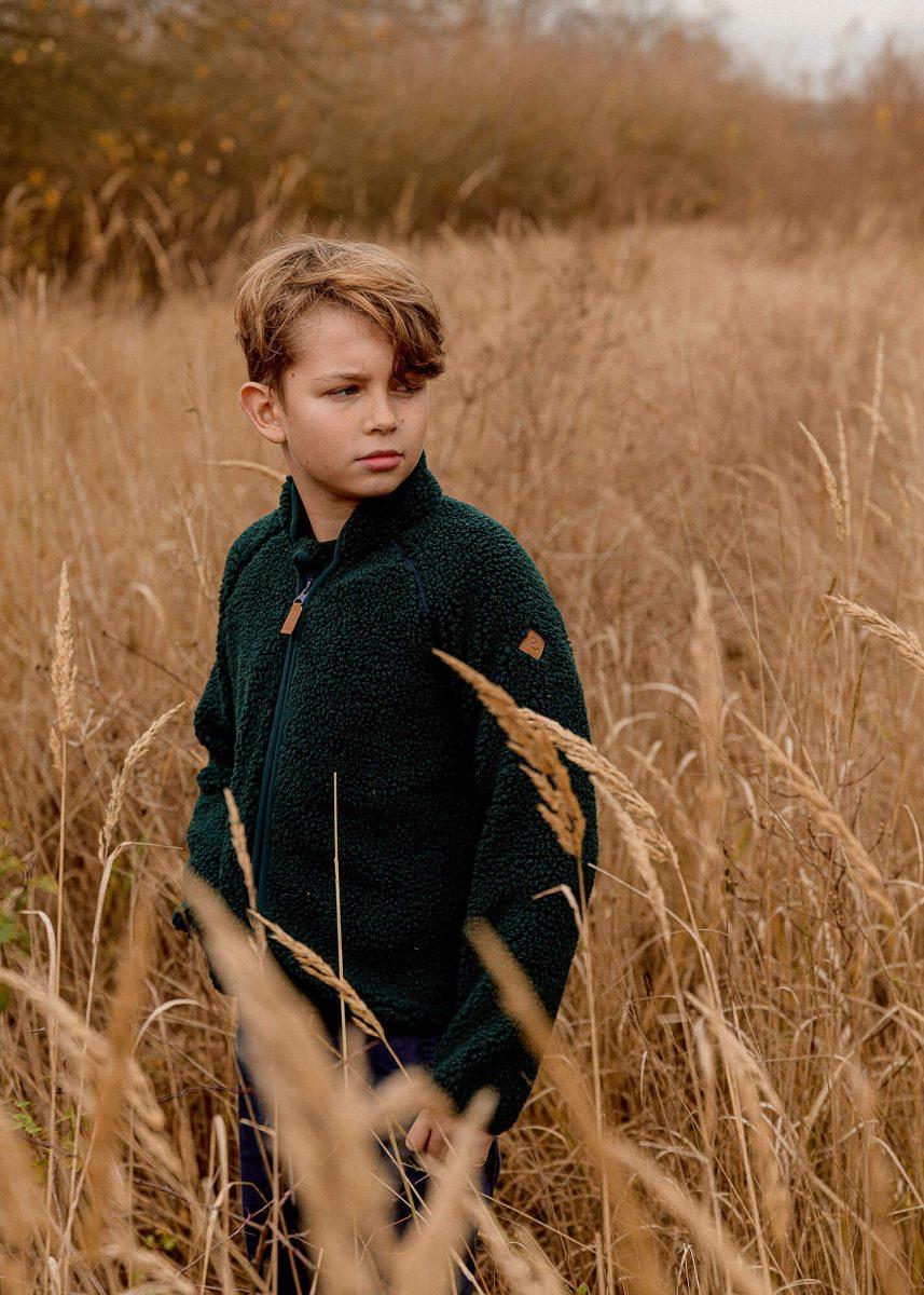 Kid posing in a field, autumn light, wearing soft green fleece