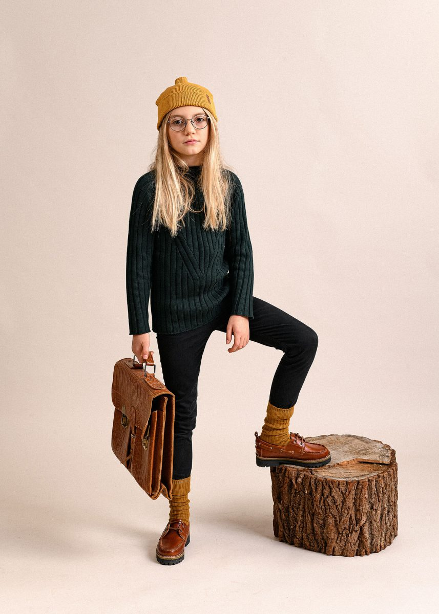 KId portrait in studio, Wearing beanie, posing, holding a bag.