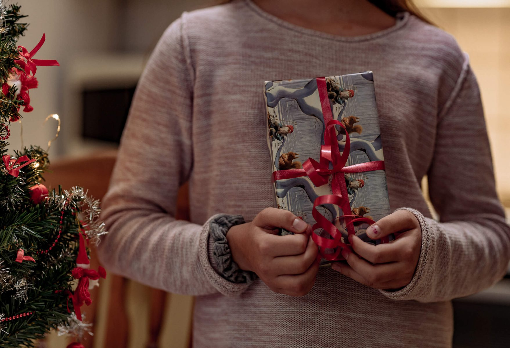 Kid holding a Christmas gift.