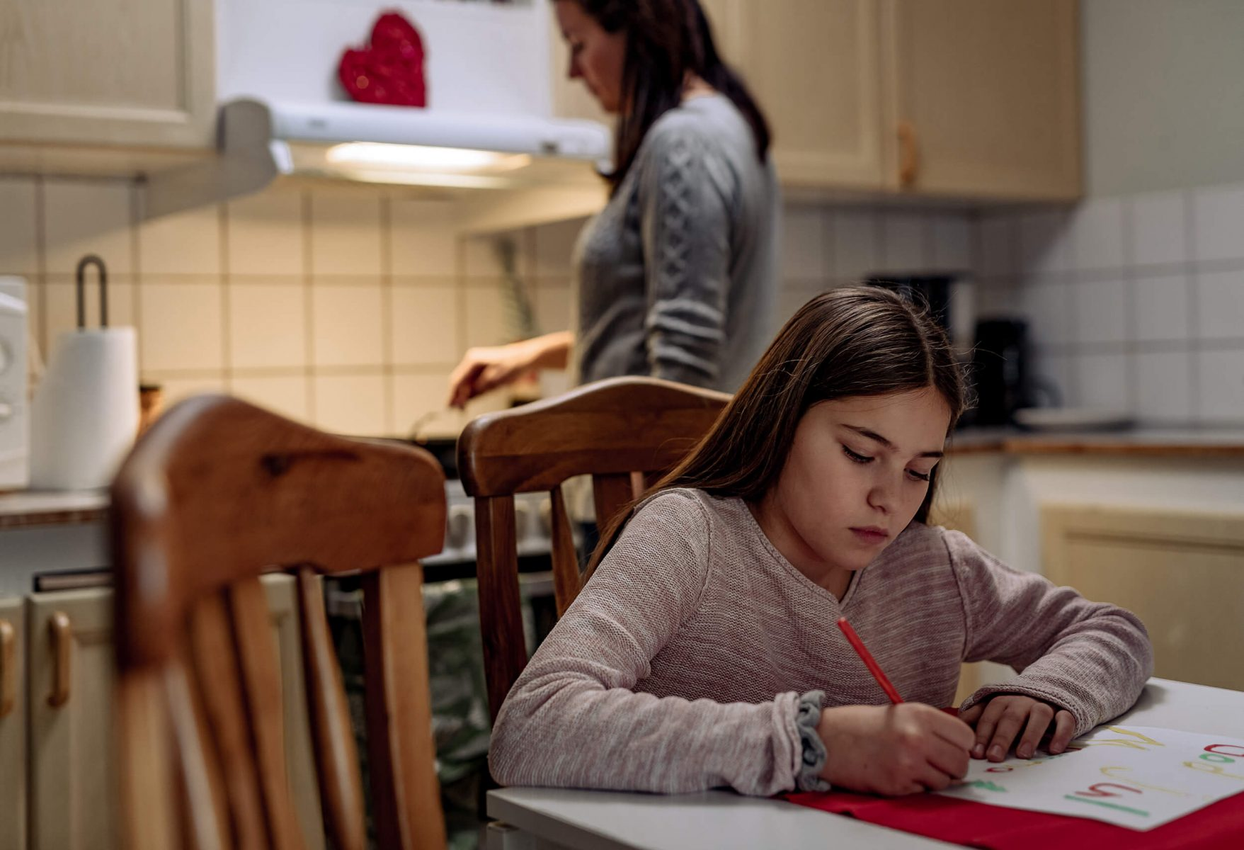 Kid making a Christmas card in kitchen. Looks bored and sad