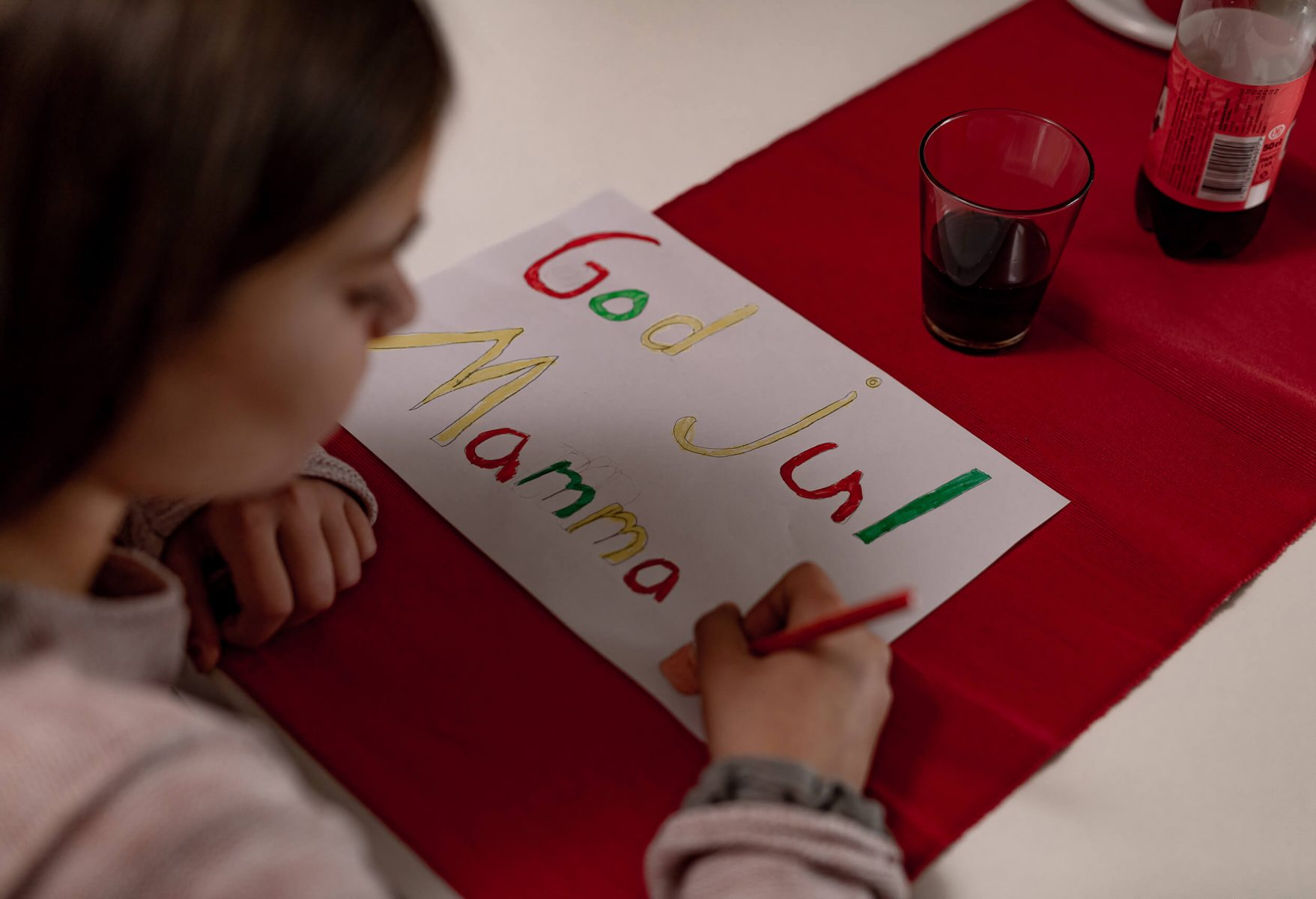 Kid making a Christmas card.