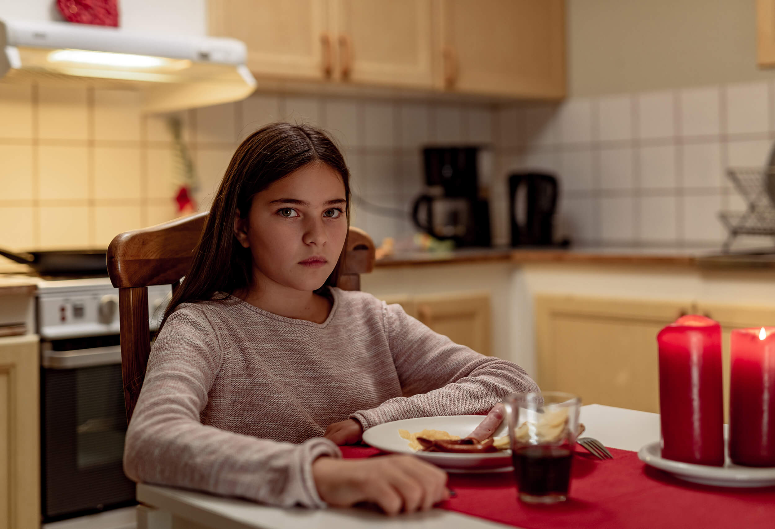 Girl sitting by table with Christmas dinner. Looks sad and bored.