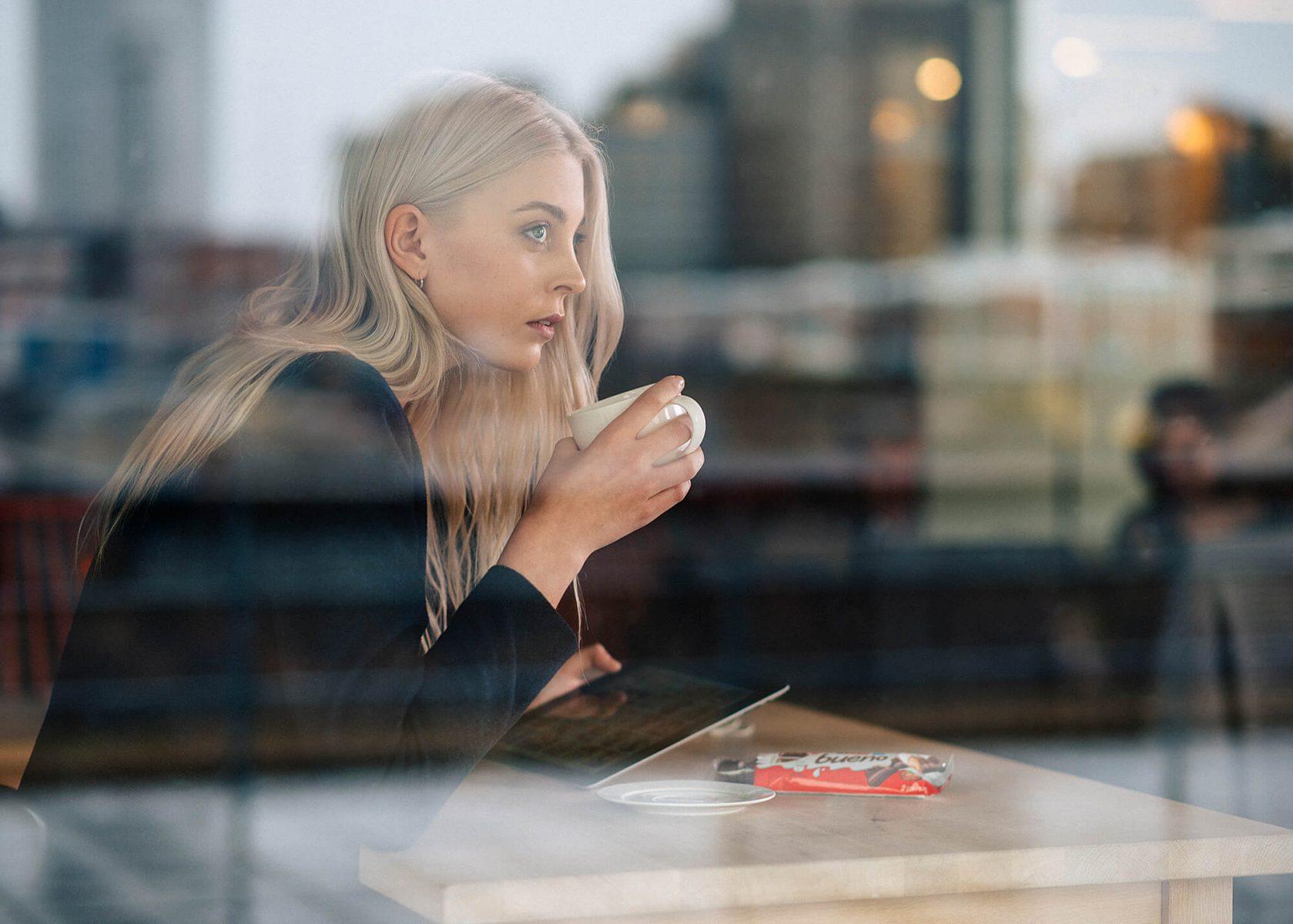 Lady drinking tea in café.