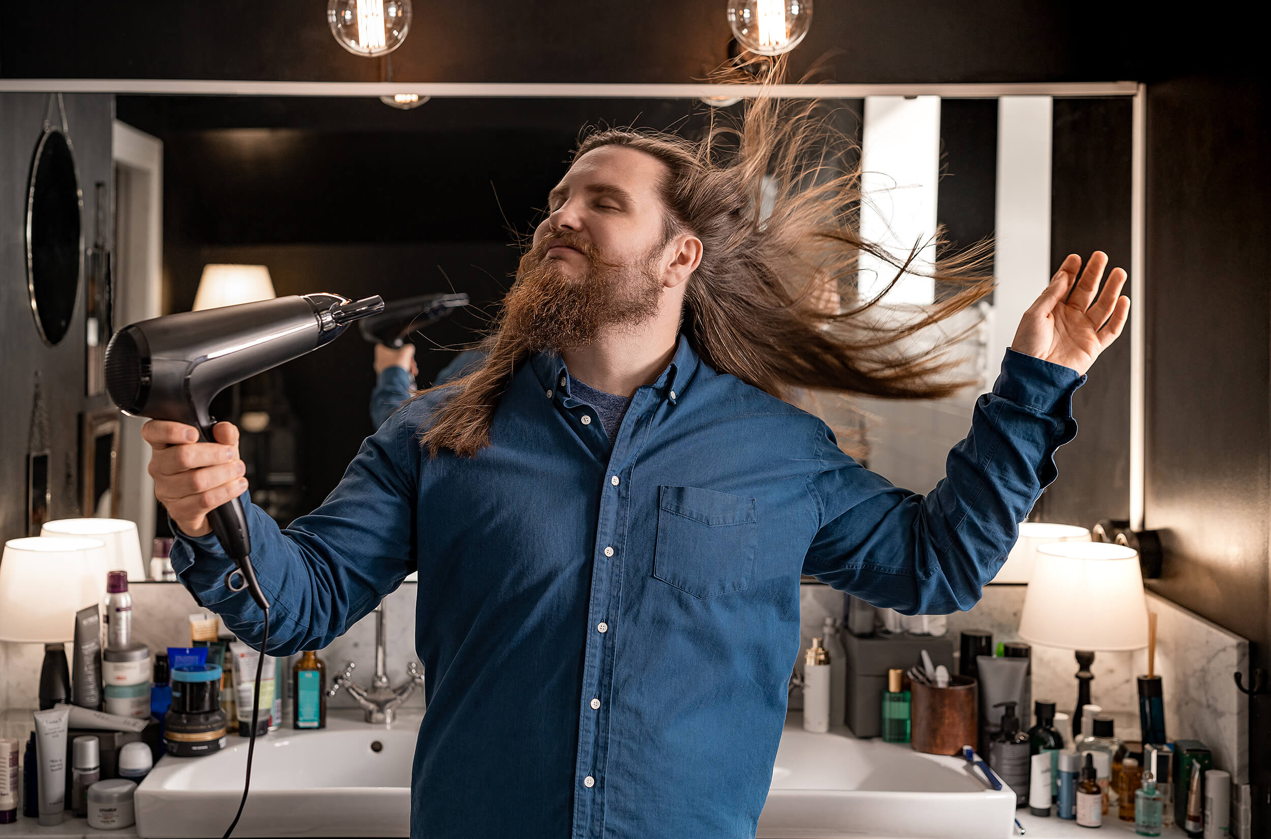 Happy bloke in bathroom. Drying his hair with a great hairdryer.