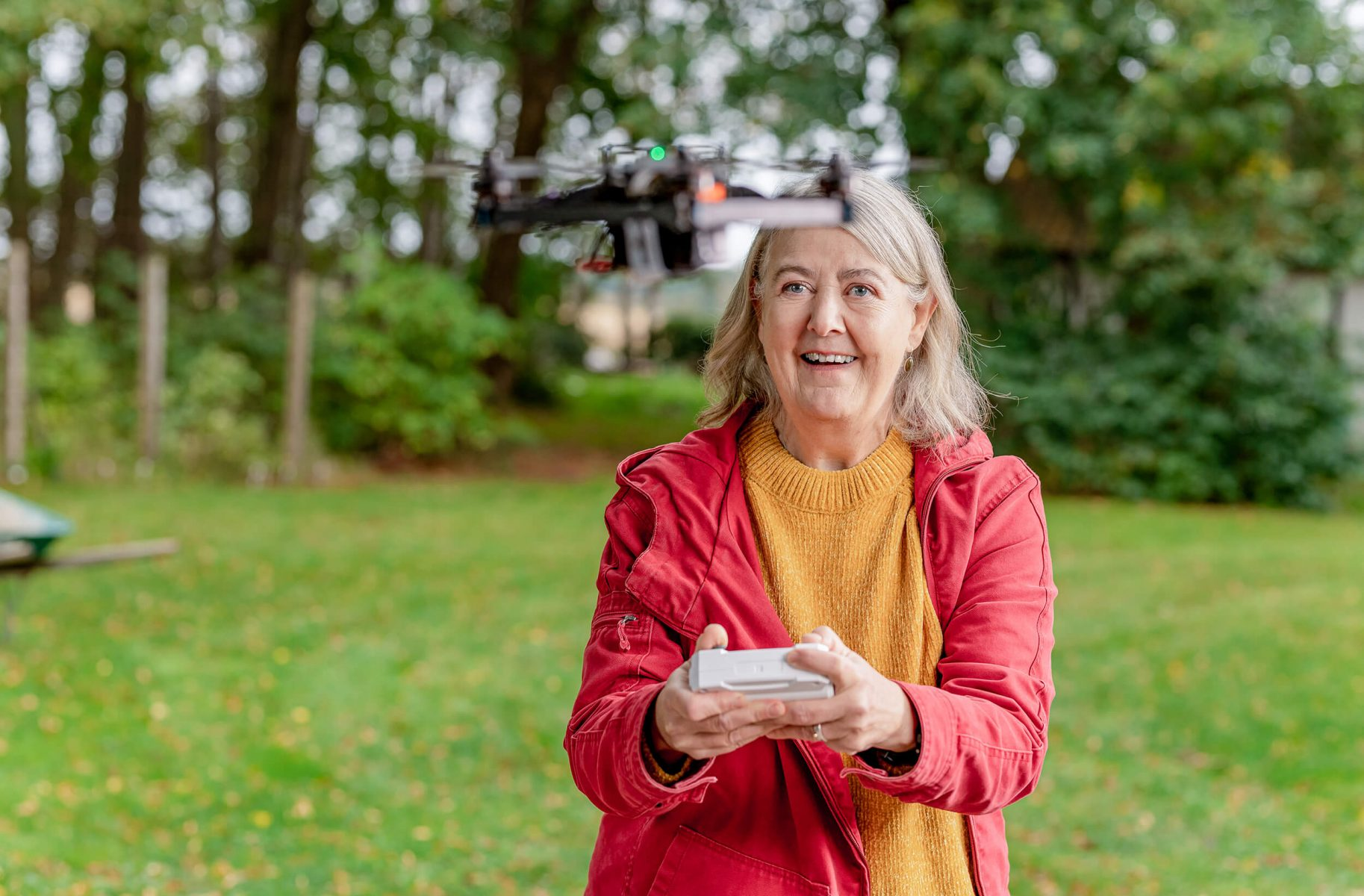 Happy lady in the garden flying drone.