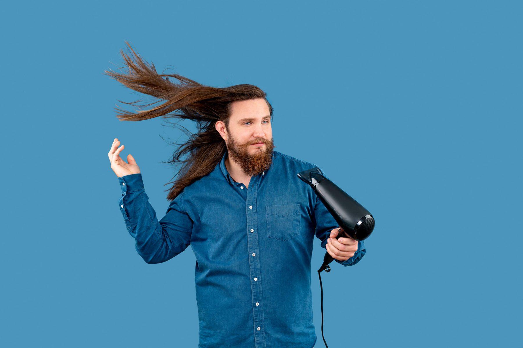Man with hairdryer in studio.