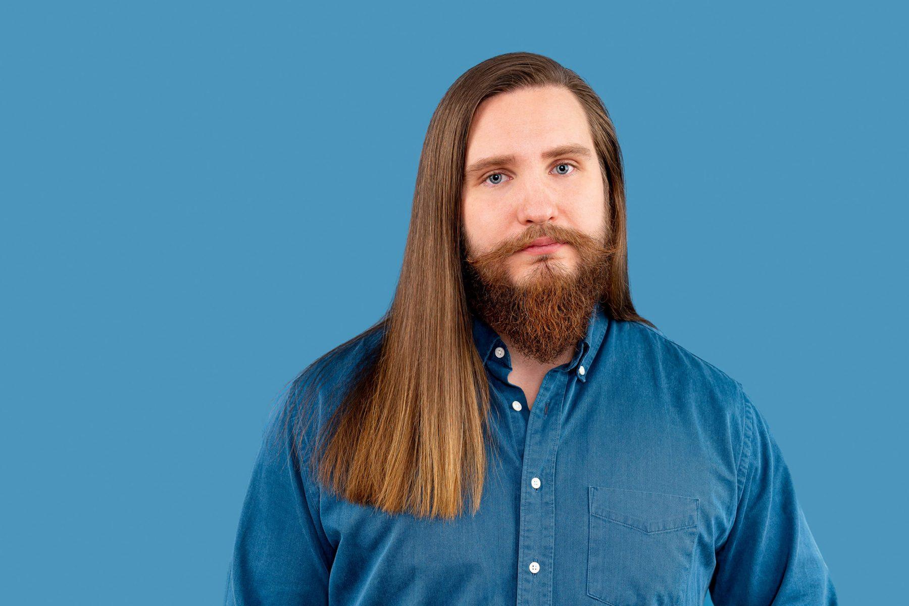 Sad man in studio. Blue background. Sad eyes.