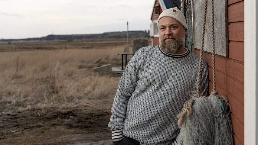 Man leaning on a wall. Soft evening light. Man has a big beard and a knitted sweater.