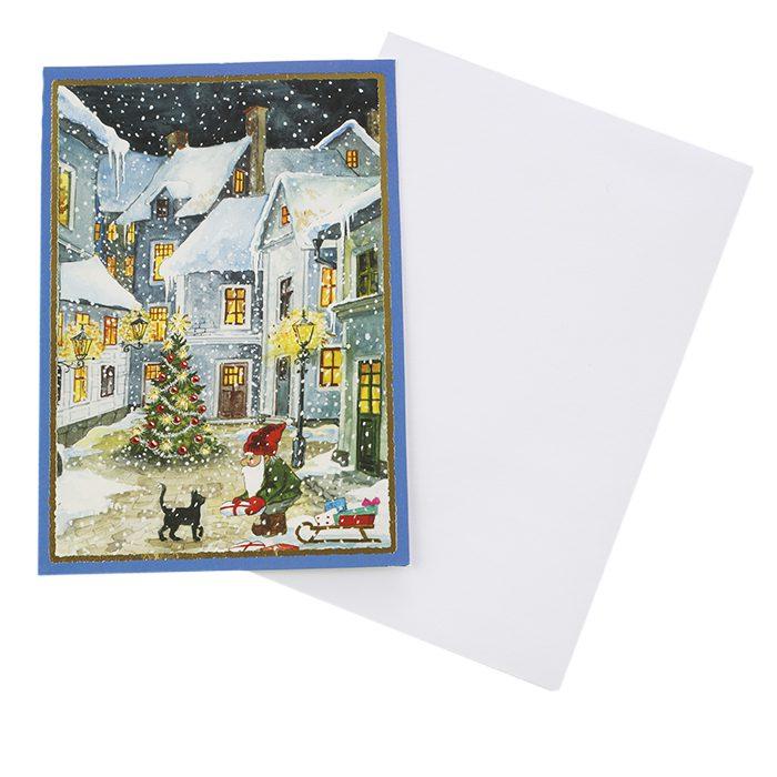 Dubbelt julkort där framsidan visas här. En gata i en stad där en tomte möter en katt och det snöar