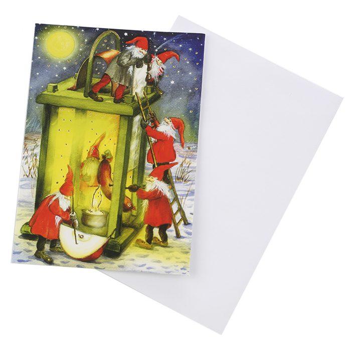 Dubbelt julkort där framsidan visas här. Många små tomtar som grillar en jättestor korv i en ljuslykta