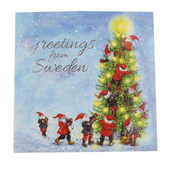 En stor gran som kläs av tomtar och text Greetings from Sweden i silver