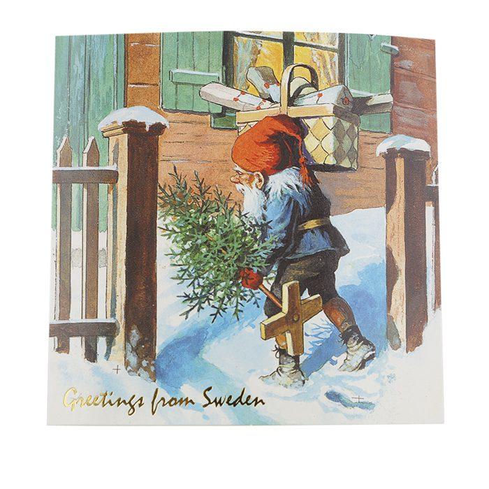 Julkort med tomte som bär på en gran och en korg med paket