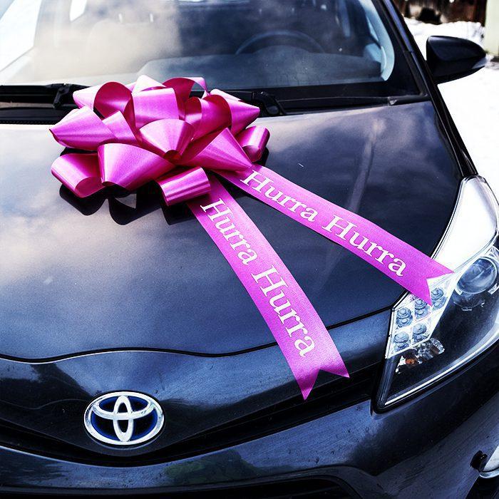 En stor lila AmericanStarRosett som ligger på motorhuven på en bil med texten hurra hurra på hängbanden