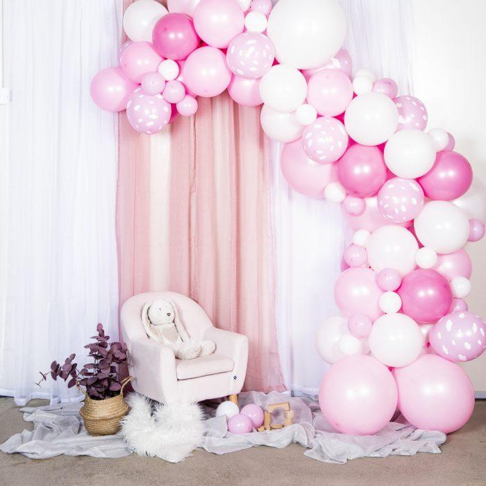 En båge med ballonger i olika storlekar. Vita och olika nyanser av rosa