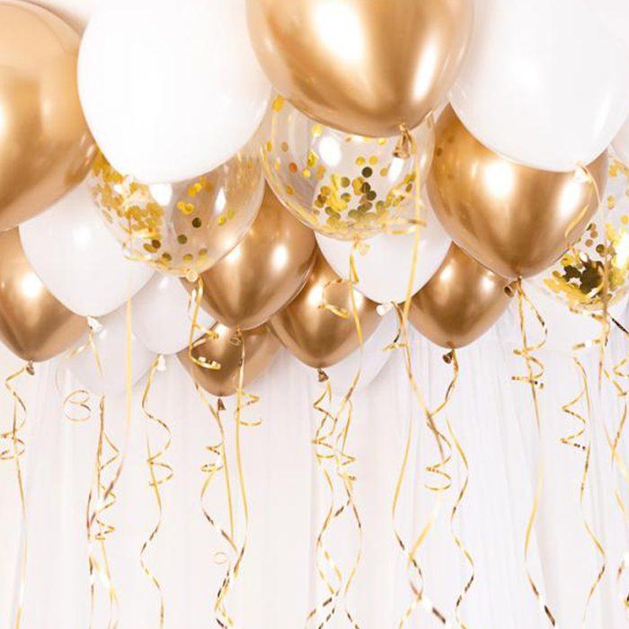 Ett tak fyllt med ballonger i guld och vitt med snören i samma färger