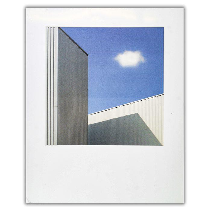 Cloud Fotograf: Henk van Maastricht En färgbild på ett ensamt moln på en blå himmel omgivet av vita höga byggnader
