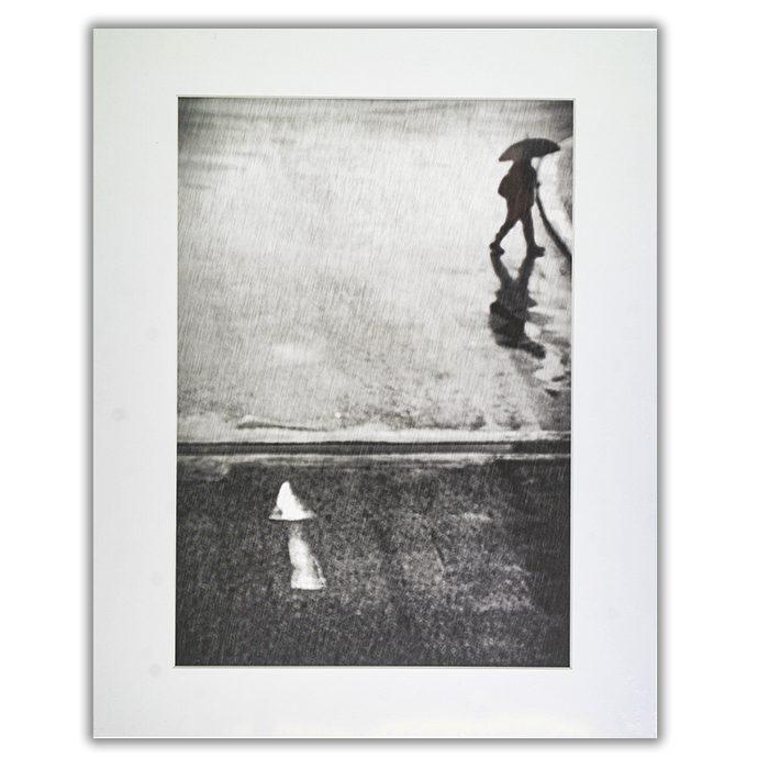 If I Have To Go Fotograf: Laura Mexia En svartvit suddig bild av regn och en person i siluett som går ut ur bilden med ett paraply