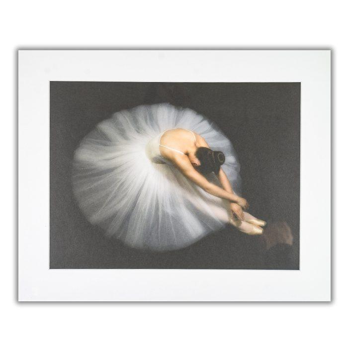 Elegance Fotograf: Pauline Pentony BA Hons ARPS En balettdansös som sitter på golvet med tyllkjolen som en cirkel runt henne, hon ligger framböjd mot sina fötter. Bakgrunden är svart