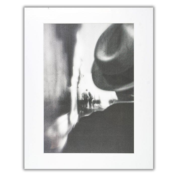 Gone Are The Days Fotograf: Laura Mexia En suddig svartvit bild av en man i hatt i förgrunden och ett par som omfamnar varandra i bakgrunden