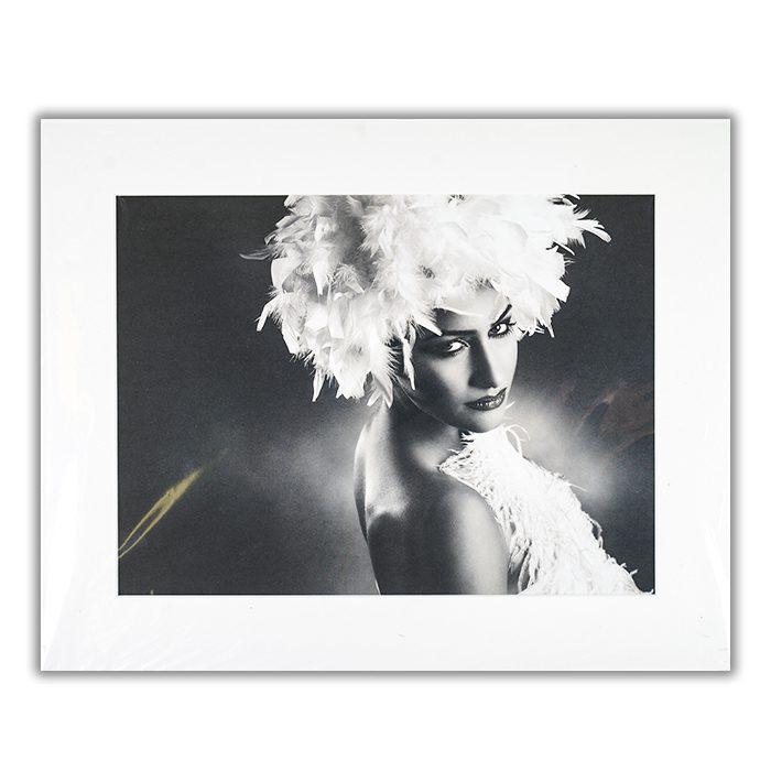 Star Fotograf: Peppe També En svartvit bild av en kvinna med en huvudbonad och klädesplagg bestående av fjädrar.