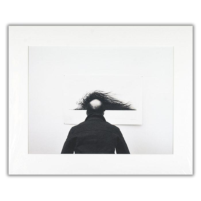 Wig Fotograf: Jorge Pena En svartvit bild av en tunnhårig man som står framför en tavla som vars motiv kan ge en illusion av att mannen har mycket hår