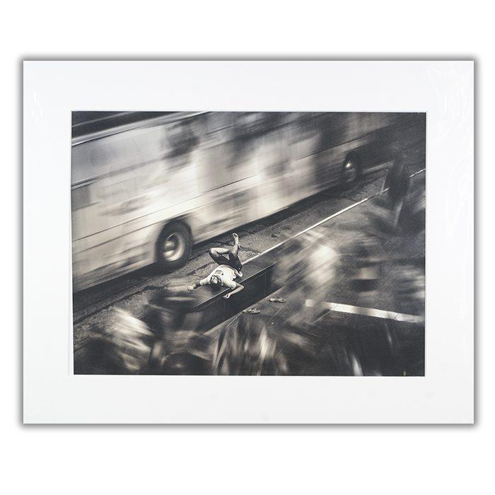 Still World Fotograf: Ali Morshedlou en svartvit bild av en man som ligger på en asfalterad väg med en buss som passerar i hög fart på ena sidan och ett hål i vägen på andra sidan. På andra sidan hålet står mannens flipflops