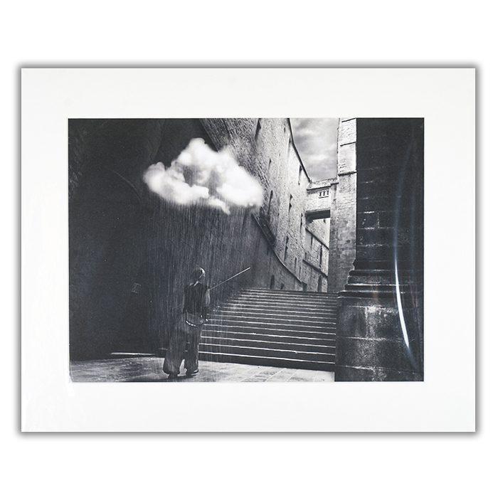 Magic Abbey 2 Fotograf: David Senechal Photographie (polydactyle) En svartvit bild av en gränd med en trappa, en person som går mot trappan och har ett moln som regnar över sitt huvud