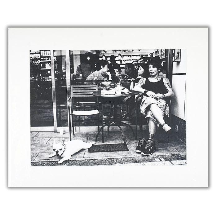 Cafe Fotograf: Tatsuo Suzuki En svartvit bild tagen i ett cafe med en person i förgrunden och flera andra i bakgrunden