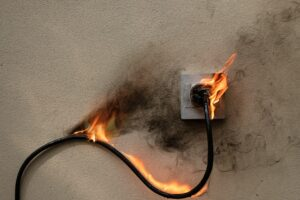 On fire electric wire plug Receptacle on the concrete wall exposed concrete background