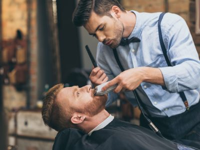 male-barber-trimming-customers-beard-in-barber-shop.jpg