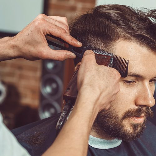 the-hands-of-young-barber-making-haircut-to-attractive-man-in-barbershop.jpg