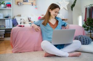 Beautiful happy young girl with laptop sitting and smiling, online dating concept