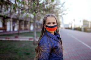 Girl wearing off the respirator medical mask in national German colors because of the end of