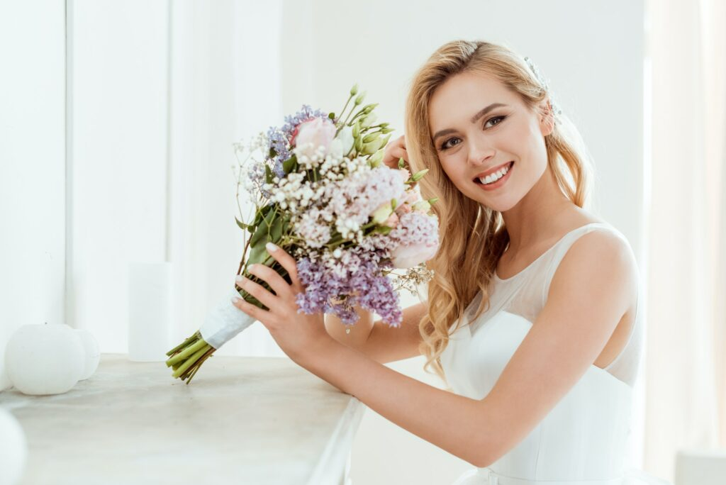smiling young bride in wedding dress with wedding bouquet