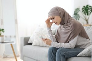 Upset Arab Girl In Hijab Looking At Smartphone Screen At Home