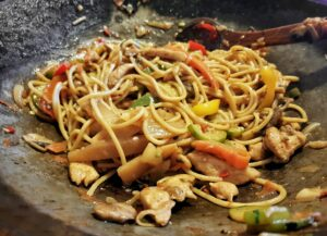 Asian food in a wok. Noodles with chicken and vegetables.