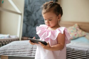 Serious little girl child indoors using mobile phone.