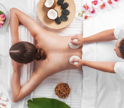 Woman at spa thai massage tow view, beauty treatments concept. Orchid and lotus flowers coconut stones and herb pouches