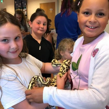 Photo of group holding a snake on Mini Beast Day.