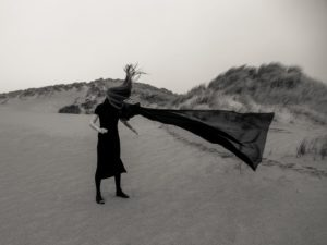 molly baber photography unearth series moody dark figure standing on windy beach