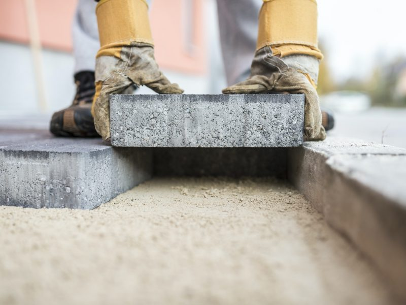 Builder laying outdoor paving slabs