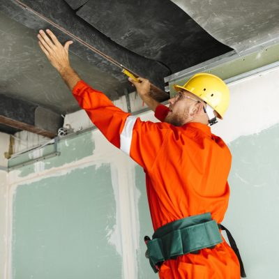 Builder in orange work clothes and yellow hardhat using measurin