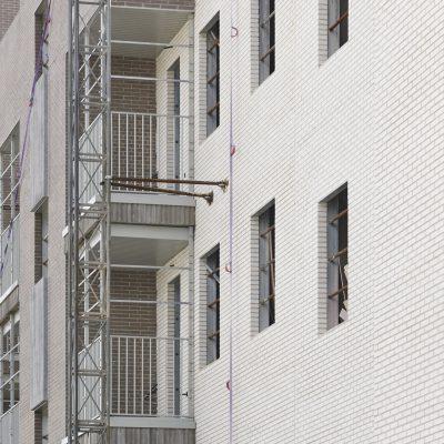 Building under construction. Brick facade structure. Architecture. Vertical
