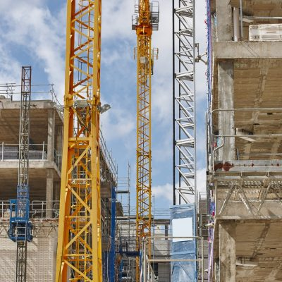 Building under construction. Crane machinery structure. Industry. Vertical