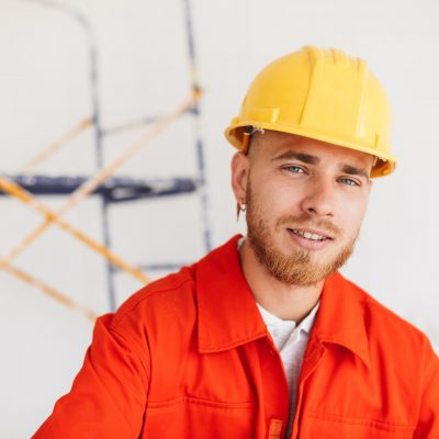 Portrait of young builder in orange work clothes and yellow hard
