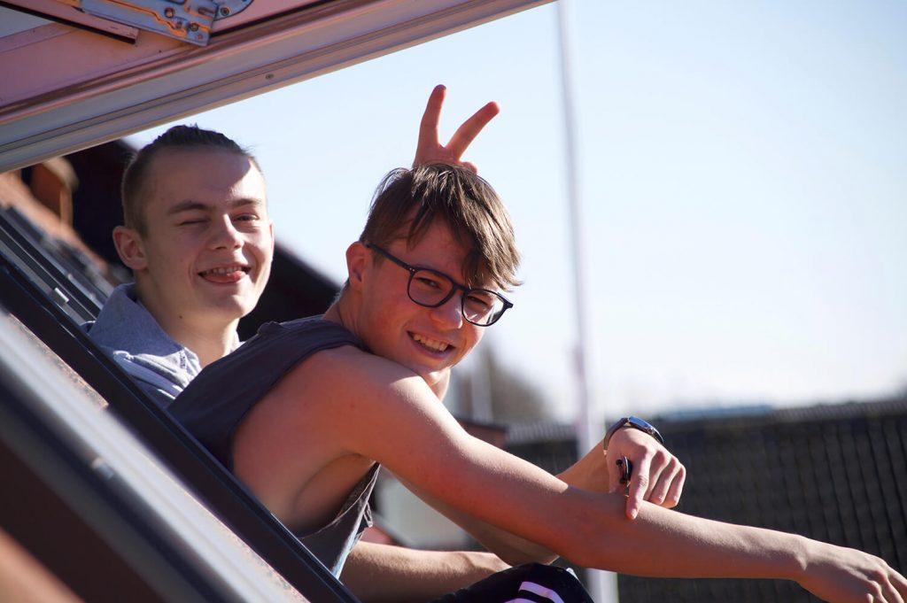 Elev laver sjov med en anden elev i vinduet. Drengestreger i 10. Klasse Basis