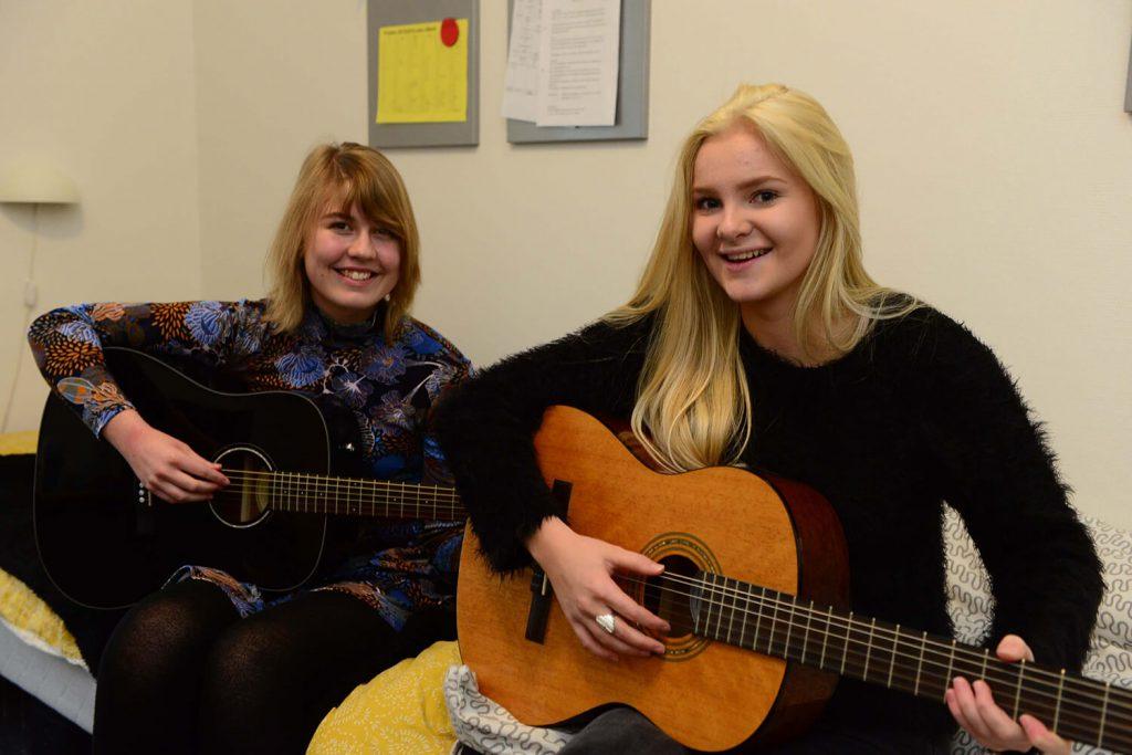2 Glade elever (piger) der spiller guitar i Musik faget